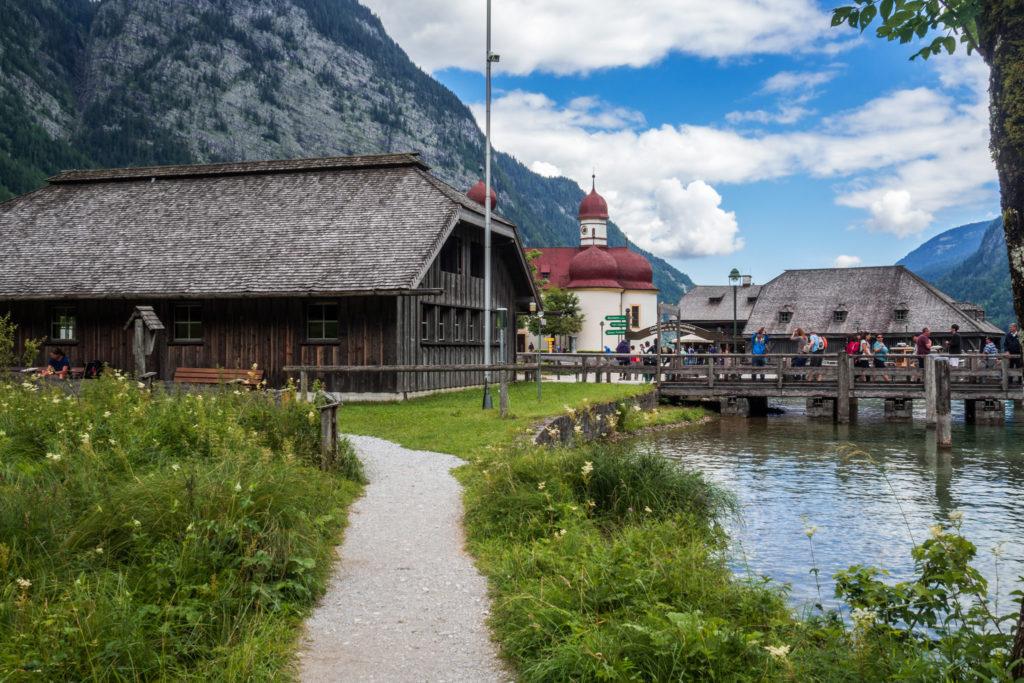 Das Bild zeigt die Bootsanlegestelle in St. Bartolomä. Im Hintergrund sind die Zwiebeltürme des alten Jagdschlößchens zu sehen.