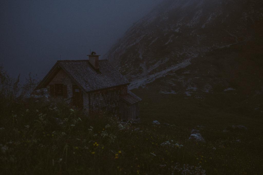 Blick auf das Winterlager am Watzmannhaus. Der Nebel verbreitet eine düstere, einsame Stimmung.