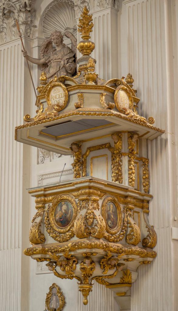 Das Bild zeigt eine Kanzel, die mit vielen Goldverzierungen geschmückt ist, in der katholischen Kirche St. Michael in München.