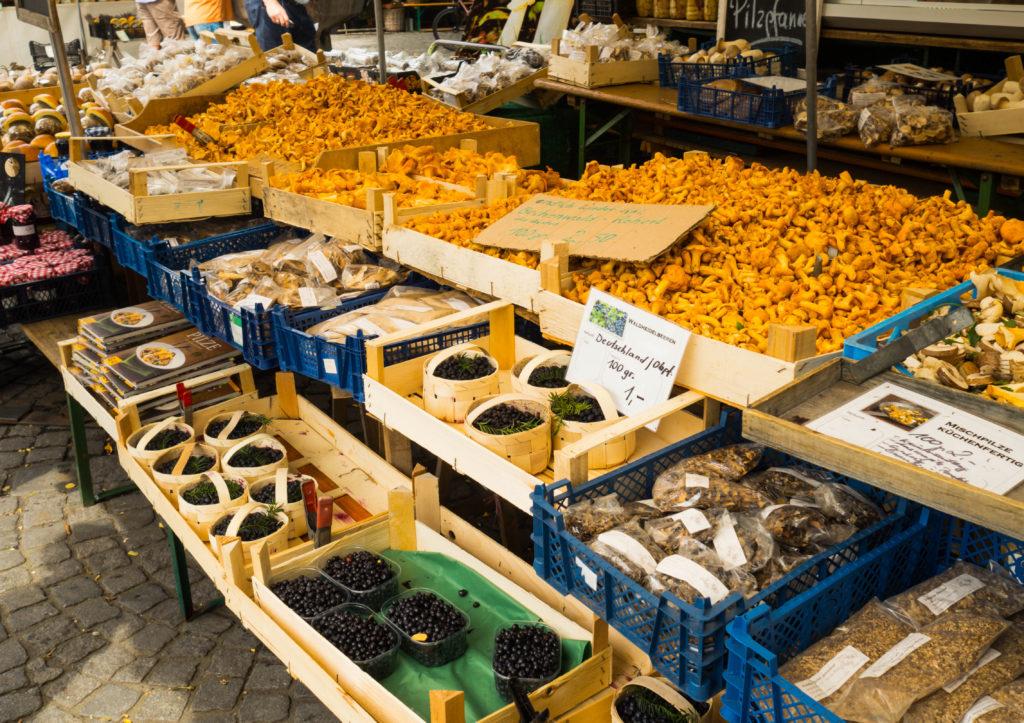 Das Bild zeigt einen typischen Stand auf dem Viktualienmarkt in München mit frischen Heidelbeeren und Pfifferlingen.