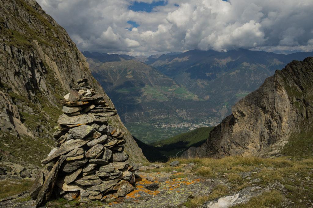 Das Bild zeigt im Vordergrund ein Steinmännchen, im Hintergrund der Blick ins Tal.
