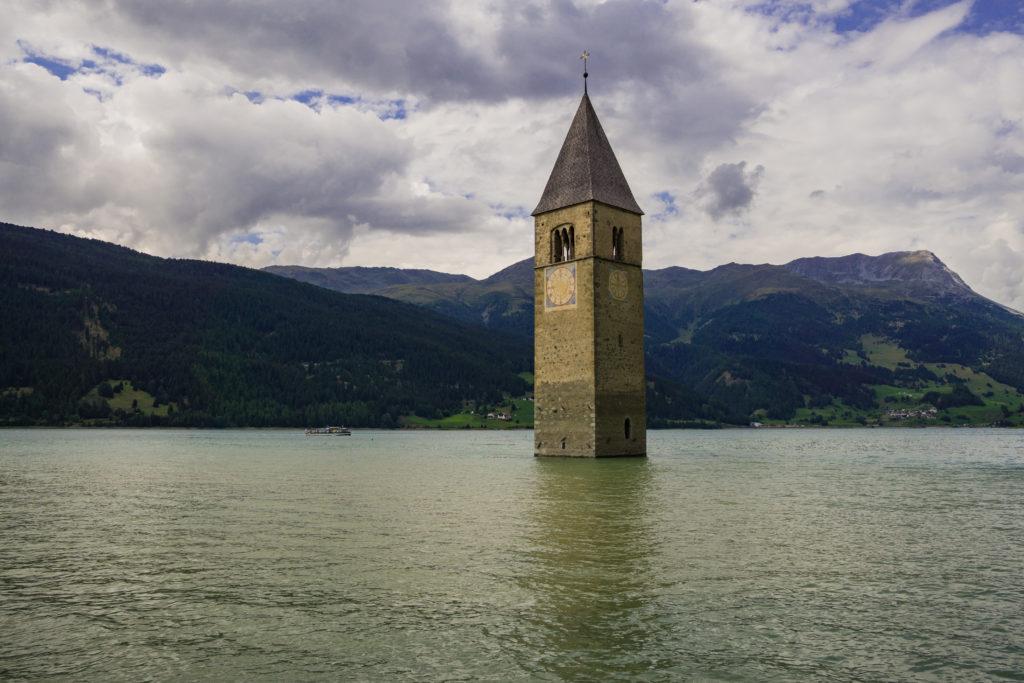 Das Bild zeigt eines der Wahrzeichen des Vinschgaus - den Reschensee mit altem Kirchturm.