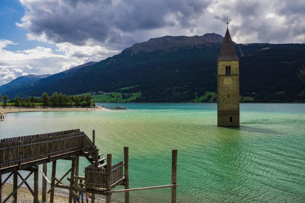 Das Foto zeigt den Kirchturm im Reschensee - eines der Wahrzeichen des Vinschgaus - und einen Holzsteg als Fotopunkt.