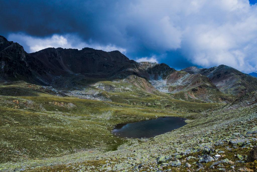 Das Bild zeigt einen kleinen, klaren Bergsee im unwirtlichen Gelände unweit des Niederjöchls mit dramatischen Wolken.