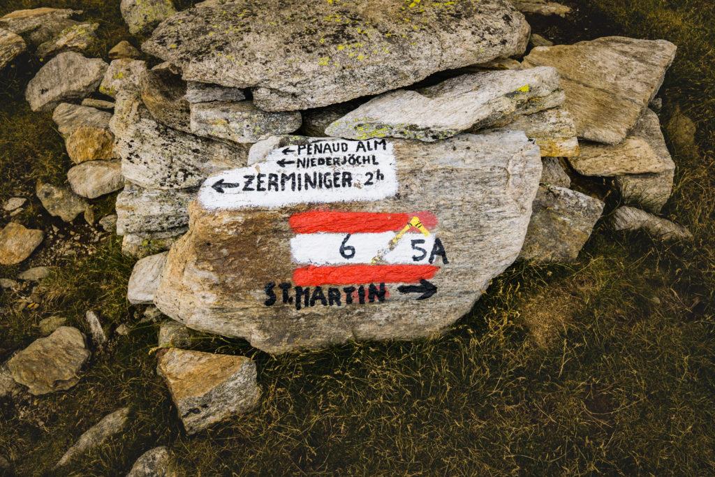 Das Bild zeigt einen großen Stein, bemalt mit Wegweisern ins Tal und zum Zerminiger.