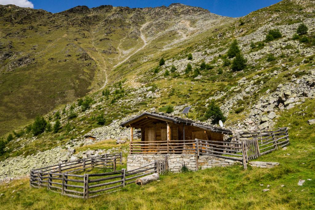 Das Bild zeigt eine Holzhütte vor einem Berg.