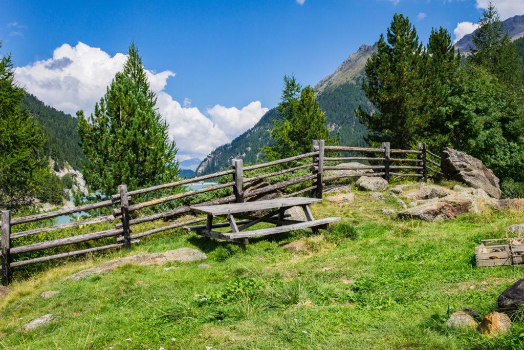 Das Bild zeigt eine Holzbank und einen Tisch, auf dem man gemütlich die Umgebung des Zufrittsees genießen kann.