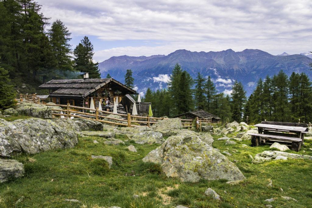 Das Foto zeigt die Latschinger Alm vor einem schönen Bergpanorama.